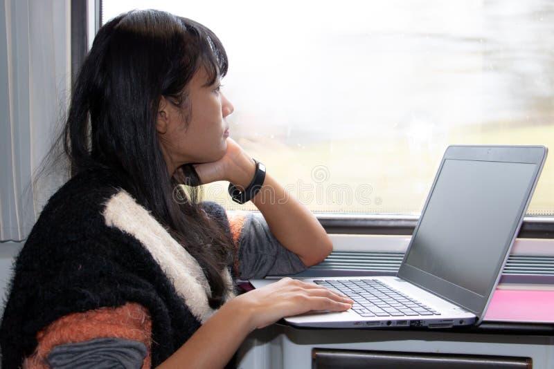研究在火车的一台计算机的年轻女人 免版税图库摄影