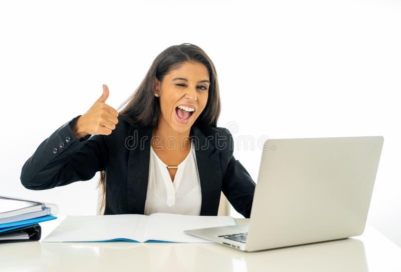 研究她的在她的书桌上的计算机的愉快的年轻女实业家在满意在白色和成功的妇女隔绝的工作 免版税库存图片