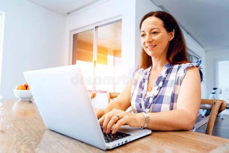 研究她的膝上型计算机的成熟美丽的妇女 免版税库存图片