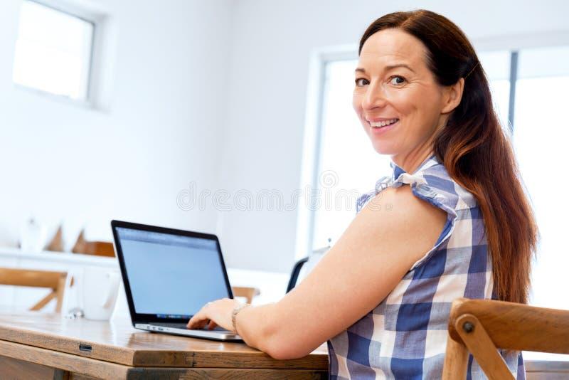 研究她的膝上型计算机的成熟美丽的妇女 免版税库存照片