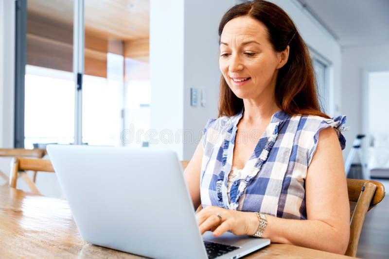 研究她的膝上型计算机的成熟美丽的妇女 库存照片