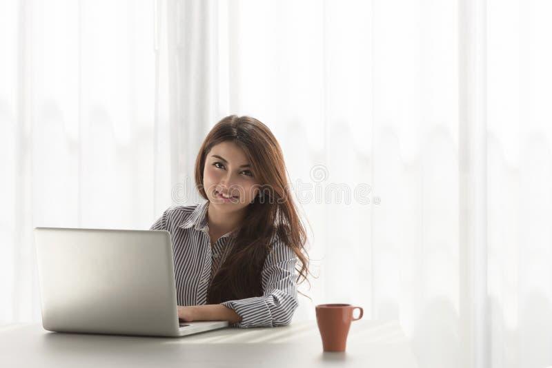 研究她的膝上型计算机的年轻亚裔妇女在她的家 免版税库存照片