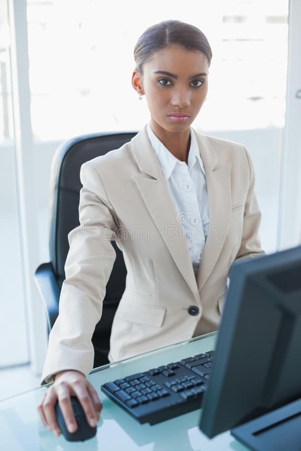 研究她的计算机的严肃的可爱的女实业家 免版税库存照片