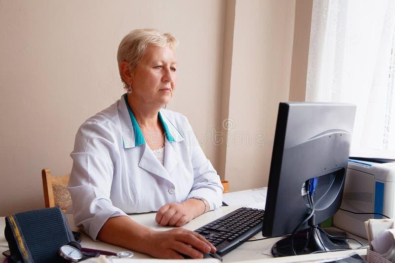 研究她的计算机的可爱的女性医生在她的办公室 免版税图库摄影
