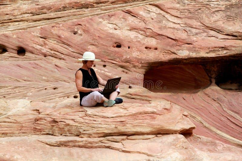 研究手提电脑上流的妇女在岩石 免版税库存图片