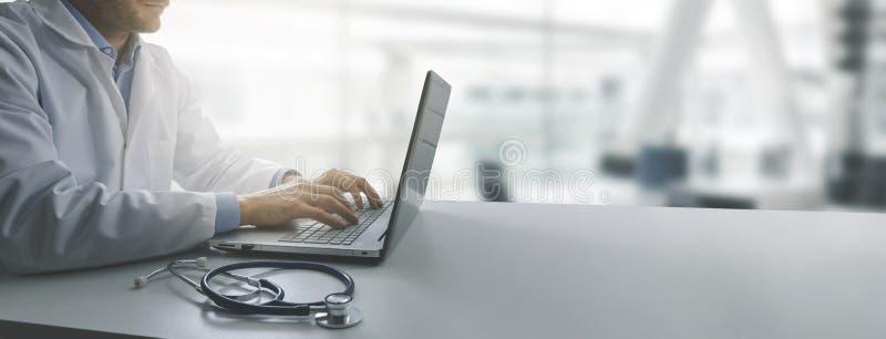 研究手提电脑的医生在现代诊所办公室 库存照片