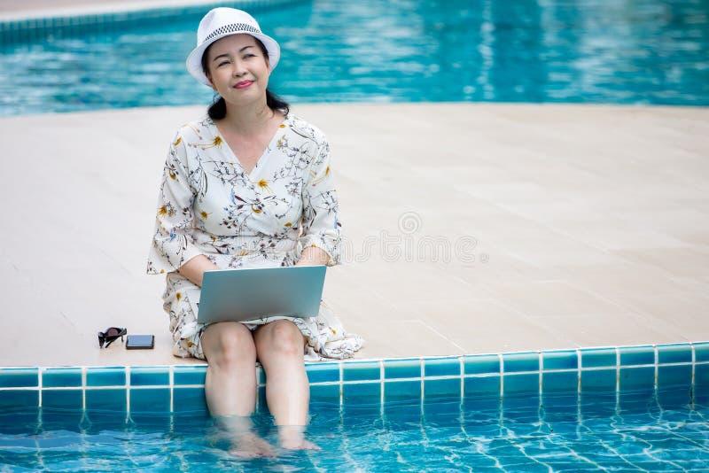 研究手提电脑的愉快的资深亚裔妇女坐在游泳池边与投入她的腿在水中 放松退休 库存图片