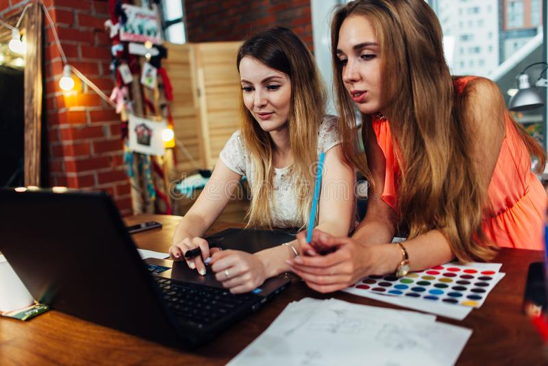 研究新的创造性的设计的两个少妇使用膝上型计算机谈论想法在舒适时髦的演播室 免版税库存图片