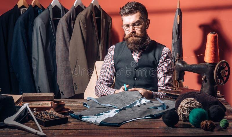 研究新的设计 缝合的机械化 有胡子的人裁缝缝合的夹克 衣服商店和