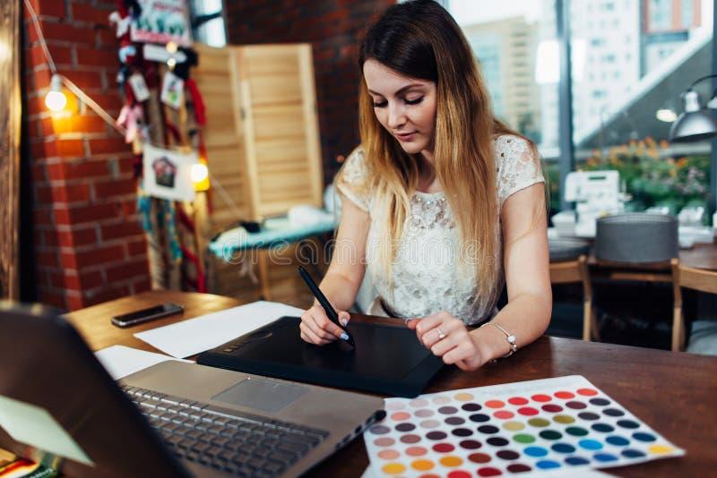 研究新的项目的年轻图表设计师画象使用坐在现代办公室的图形输入板和膝上型计算机 免版税库存图片