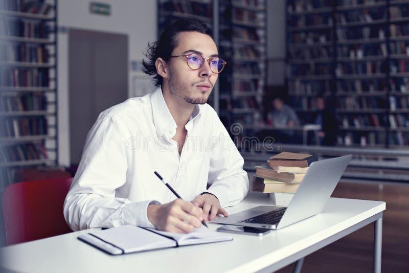 研究有书的膝上型计算机的年轻企业家或大学生在科学论文在图书馆里 库存照片