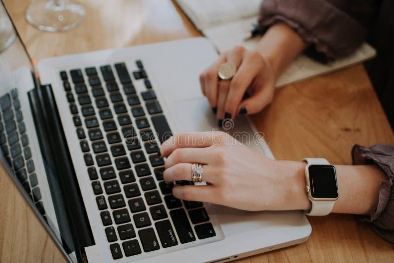 研究有传感器手表和圆环的一台膝上型计算机的女性的手 库存图片