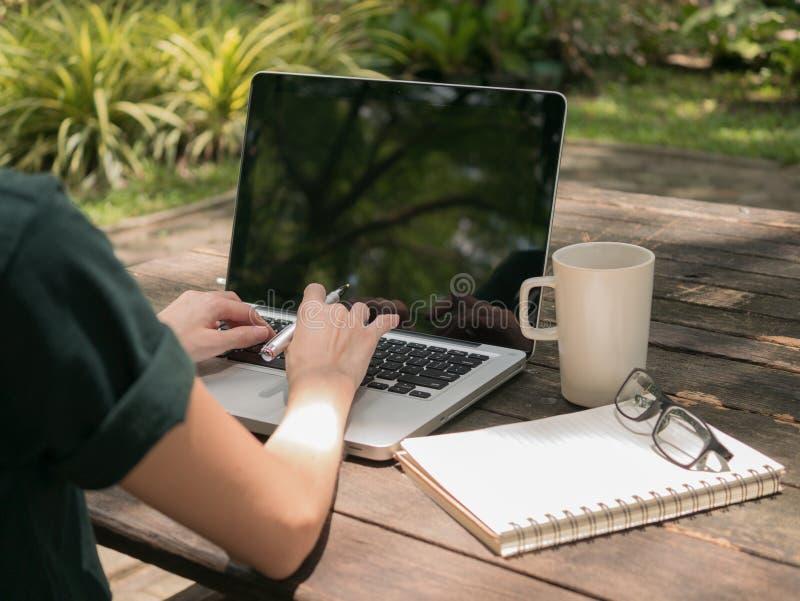 研究有加奶咖啡杯子的便携式计算机的自由职业者在木书桌上在庭院里 免版税库存照片