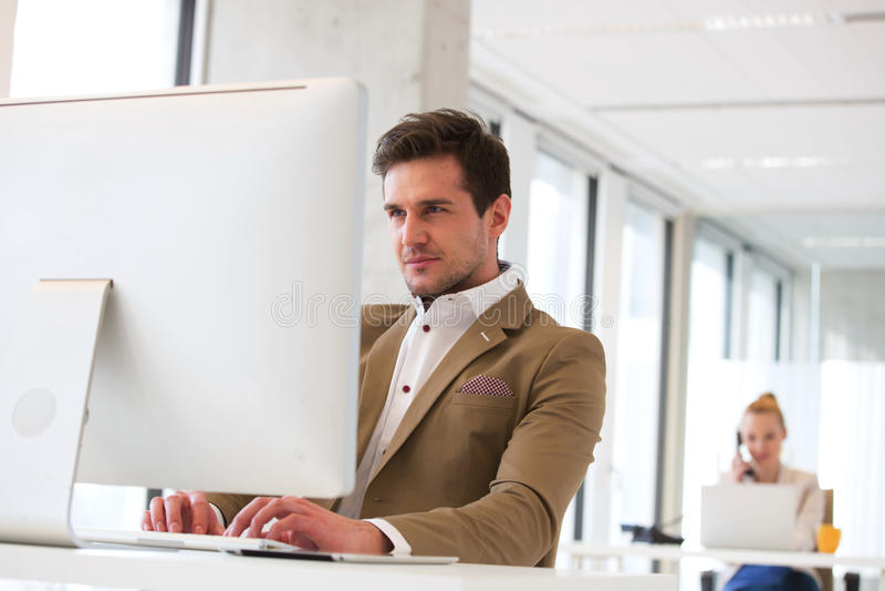 研究有女性同事的计算机的确信的年轻商人在背景中在办公室 库存图片