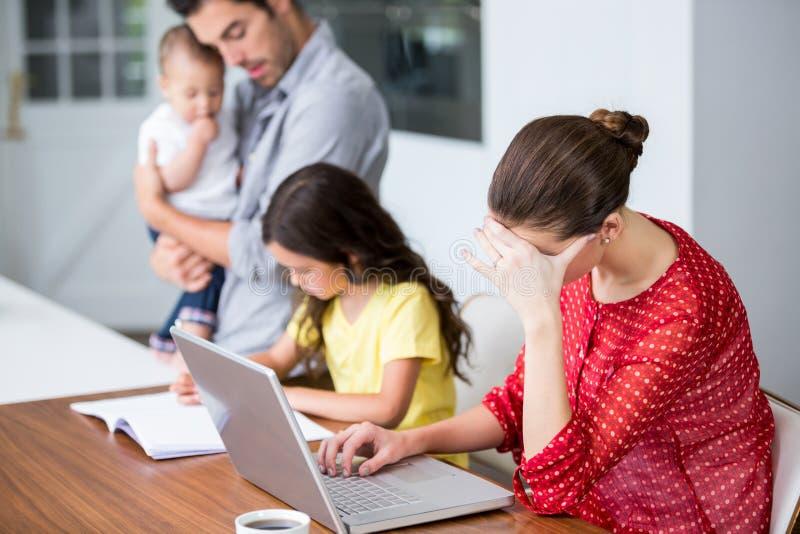 研究有父亲帮助的女儿的膝上型计算机的被拉紧的母亲家庭作业的 免版税图库摄影