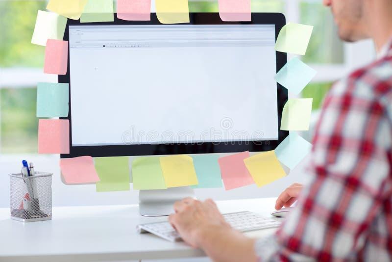 研究有稠粘的笔记的计算机的人 免版税库存照片