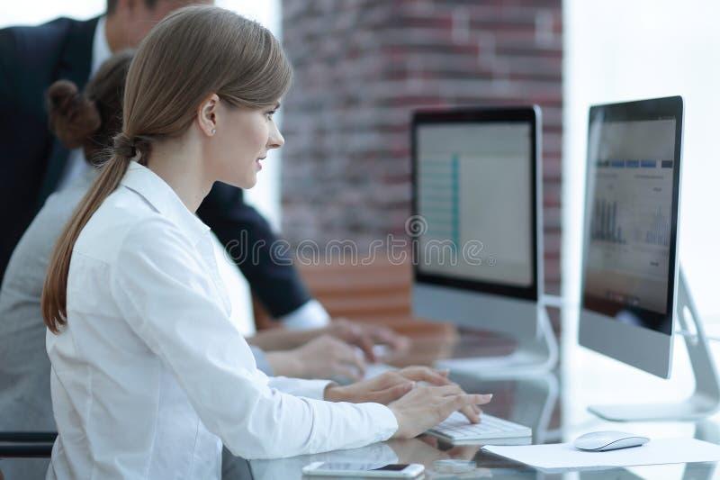 研究有财务数据的个人计算机的雇员 免版税库存照片