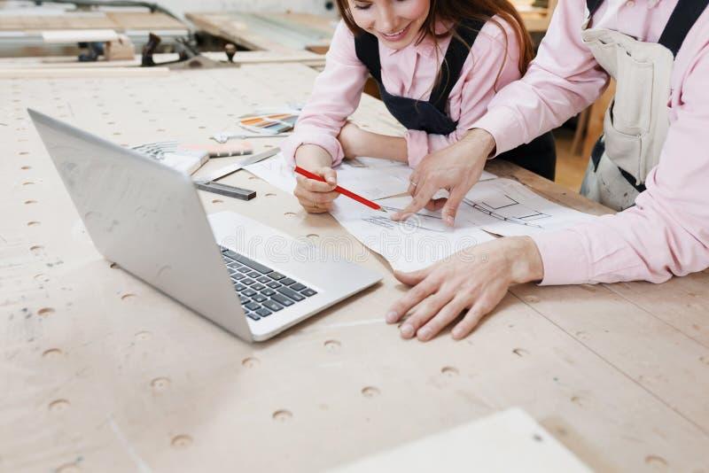 研究木表面上的膝上型计算机的女实业家木匠在建筑工具中 附近智能手机,膝上型计算机,剪贴板 库存图片