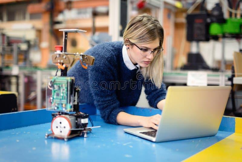 研究机器人学项目的少妇工程师 免版税库存照片