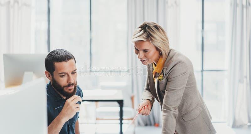 研究流动手提电脑的两个年轻工友照片在办公室 指向在屏幕的妇女 库存照片