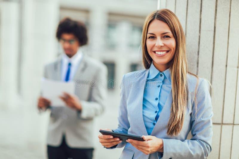 研究片剂计算机的女实业家在办公室外 免版税库存图片