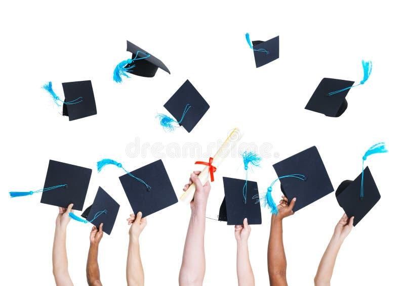 研究生投掷的毕业帽子 免版税库存照片