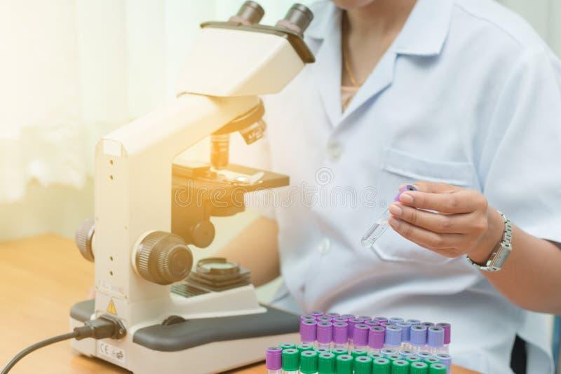 研究的设备在科学实验室、显微学和空的真空血液管,显微镜试验在医学实验室, 免版税库存照片