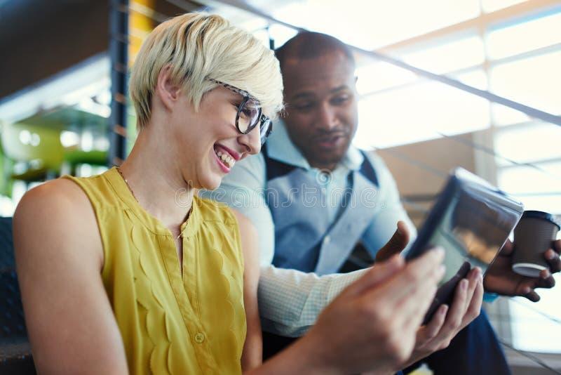 研究社会媒介战略的两个创造性的millenial小企业主使用一种数字式片剂,当参加时 免版税库存照片