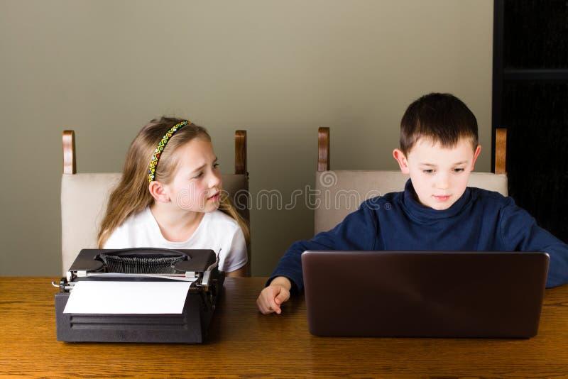 研究老打字机和膝上型计算机的孩子 库存照片