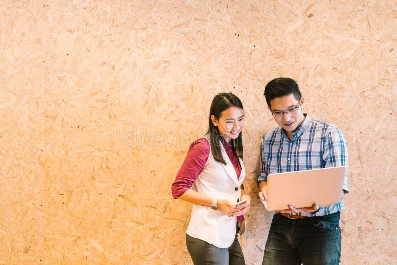 研究膝上型计算机、偶然企业同事或者信息技术概念的年轻亚裔夫妇或工友,与拷贝空间 免版税库存图片