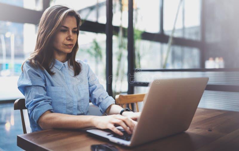 研究膝上型计算机和使用流动智能手机的年轻俏丽的女孩在她的工作场所在现代办公室中心 水平 免版税库存图片