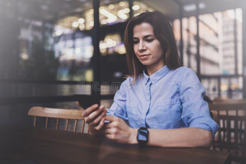 研究膝上型计算机和使用流动智能手机的年轻俏丽的女孩在她的工作场所在现代办公室中心 水平 图库摄影