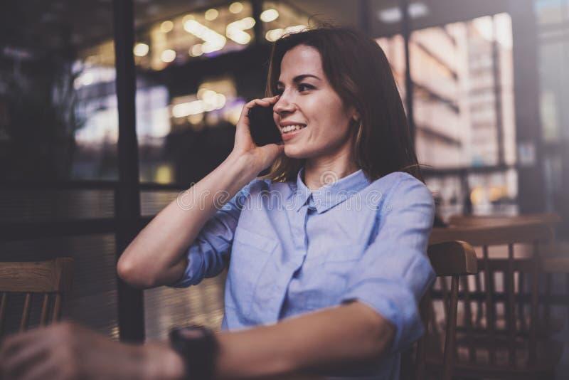 研究膝上型计算机和使用流动智能手机的年轻俏丽的女孩在她的工作场所在现代办公室中心 水平 库存图片
