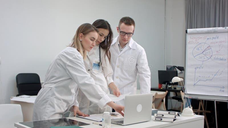 研究膝上型计算机和分析X-射线的医生队在医疗办公室 免版税库存图片