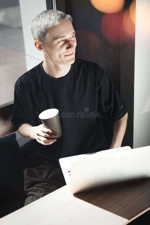 研究膝上型计算机和拿着一杯咖啡的年轻微笑的人 免版税库存图片