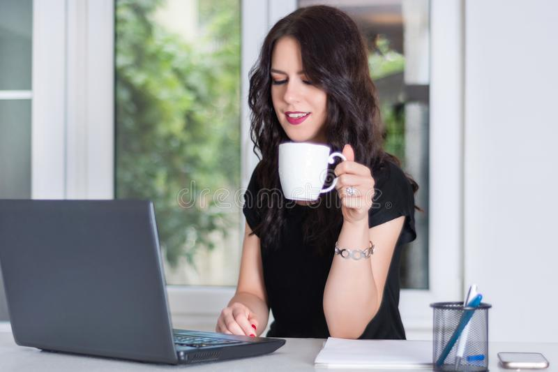 研究膝上型计算机和拿着咖啡的年轻和逗人喜爱的女商人 免版税库存图片