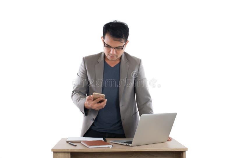 研究膝上型计算机和拿着智能手机的商人,白色 库存图片
