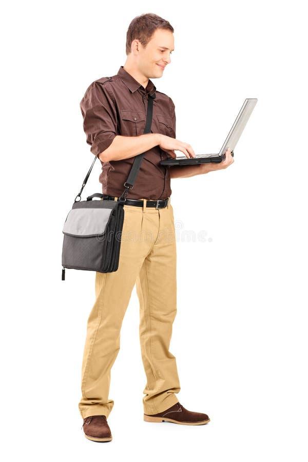 研究膝上型计算机的一个年轻人的全长画象 库存照片