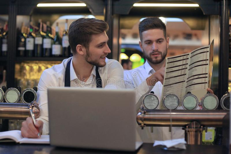 研究膝上型计算机的两位愉快的咖啡馆经理 库存图片