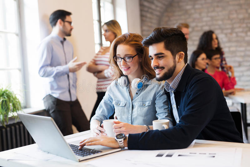 研究膝上型计算机的两位年轻建筑师在办公室 免版税库存图片