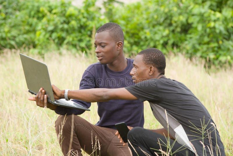 研究膝上型计算机的两年轻人户外 免版税图库摄影