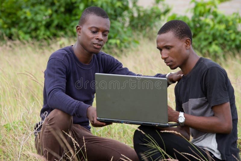 研究膝上型计算机的两年轻人户外 免版税库存图片