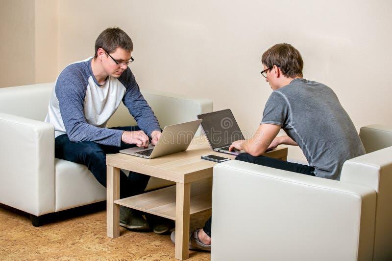 研究膝上型计算机的两青年人在办公室,写节目,改正文本 坐在彼此对面的桌上 库存照片