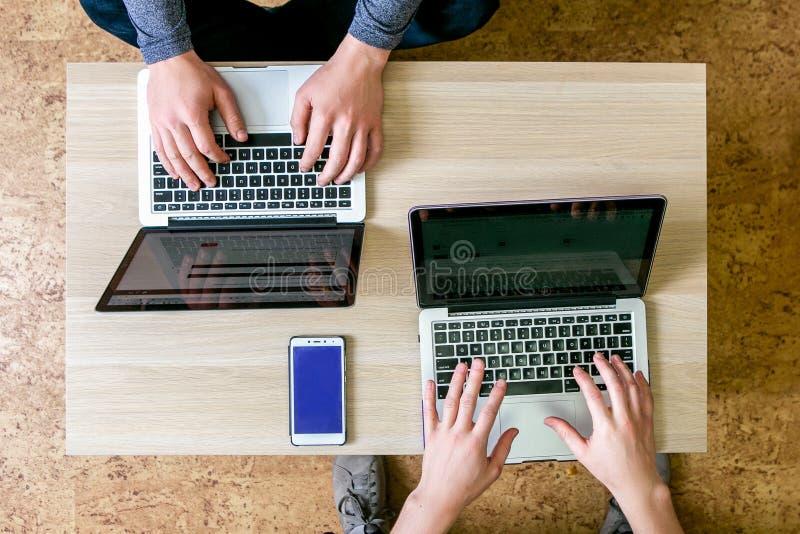 研究膝上型计算机的两青年人在办公室,写节目,改正文本 坐在彼此对面的桌,上面上 免版税库存照片