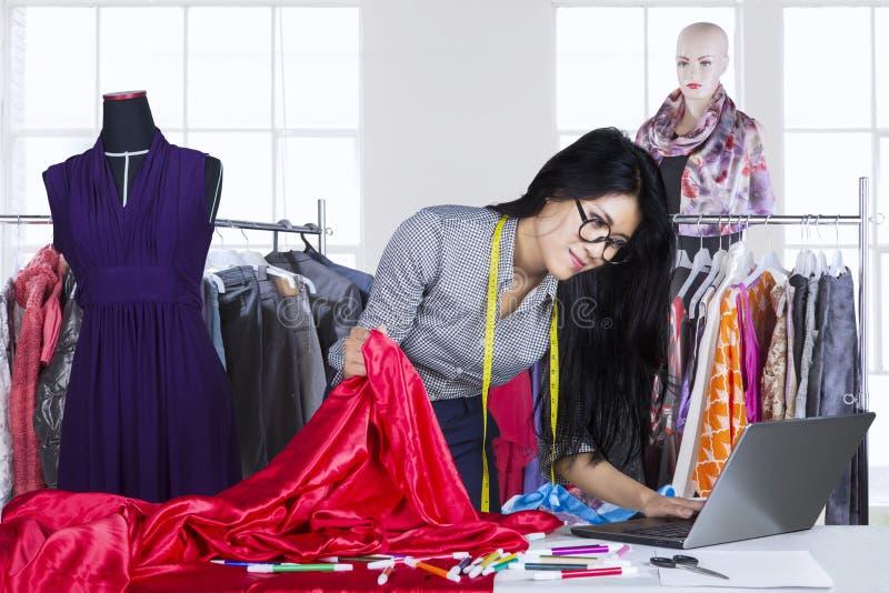研究膝上型计算机的亚裔时装设计师 免版税库存照片