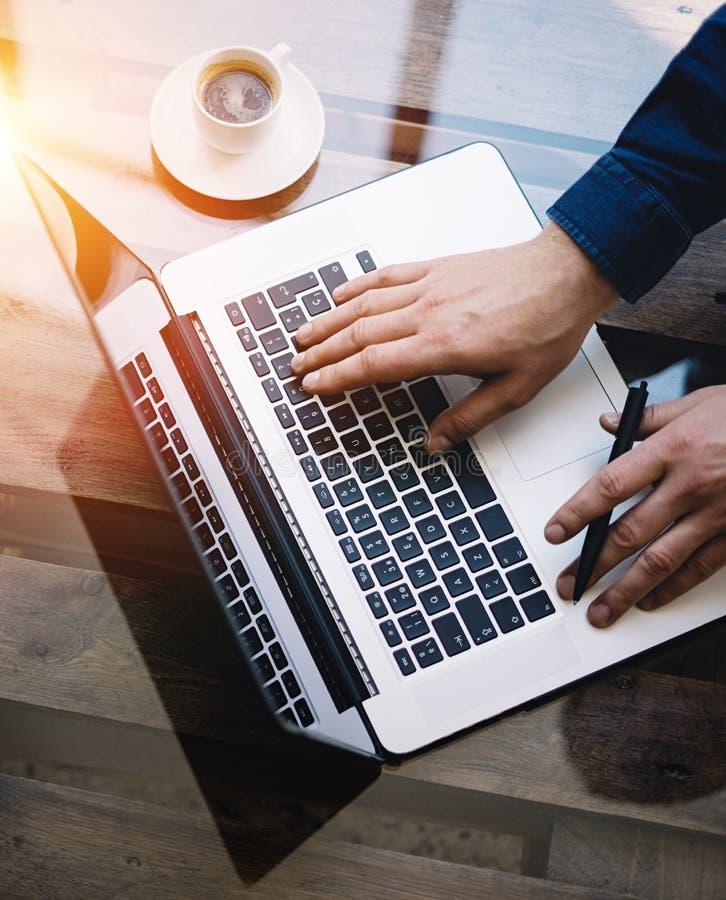 研究膝上型计算机的人在晴朗的办公室 键入在键盘的男性手 现代笔记本,杯子在木的无奶咖啡 免版税库存图片