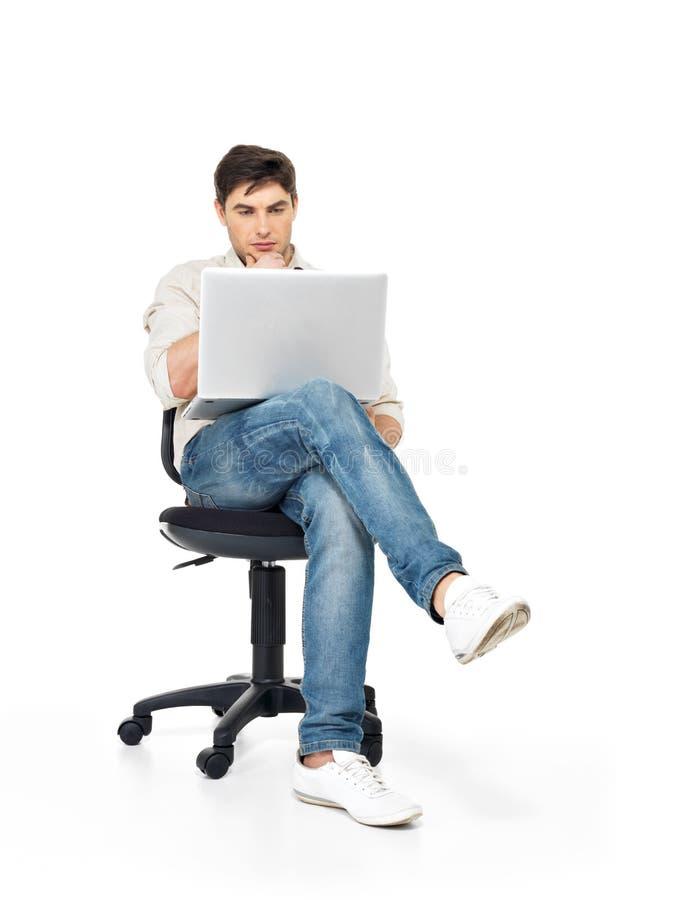 研究膝上型计算机的人坐椅子 库存图片