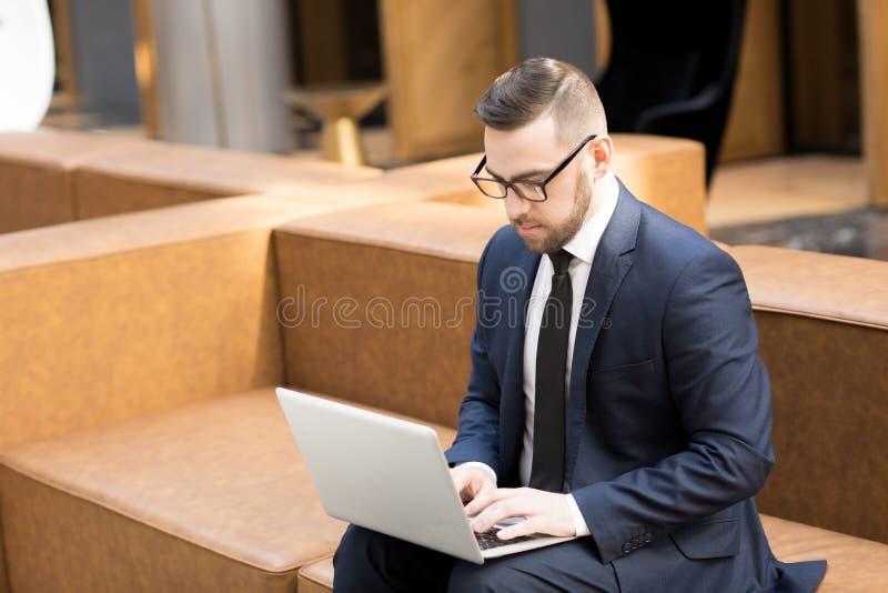 研究膝上型计算机的典雅的人在大厅里 图库摄影