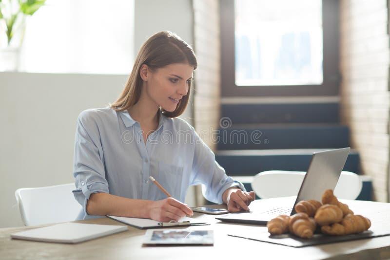 研究膝上型计算机的可爱的妇女 免版税库存照片