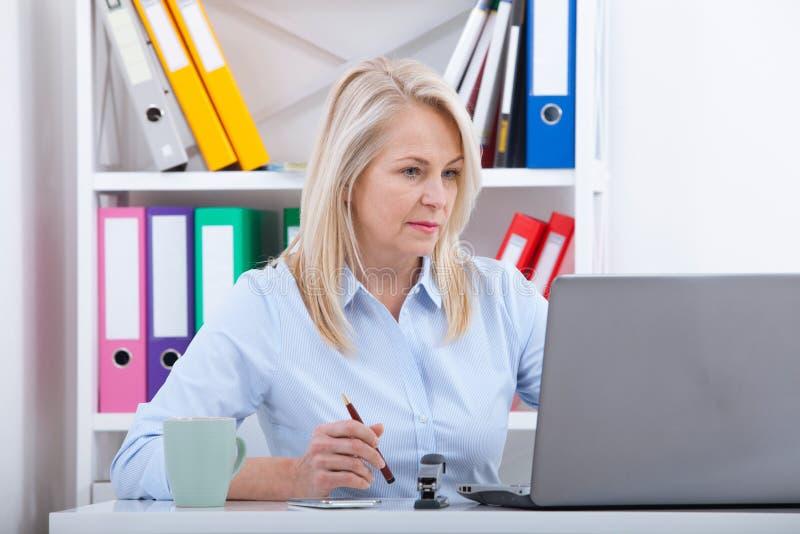 研究膝上型计算机的可爱的成熟女实业家在她的工作场所 库存照片